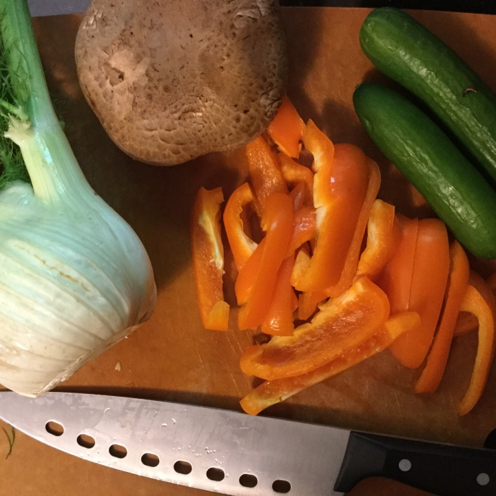 Cutting board, chef knife, fennel, portobello, cucumbers, peppers
