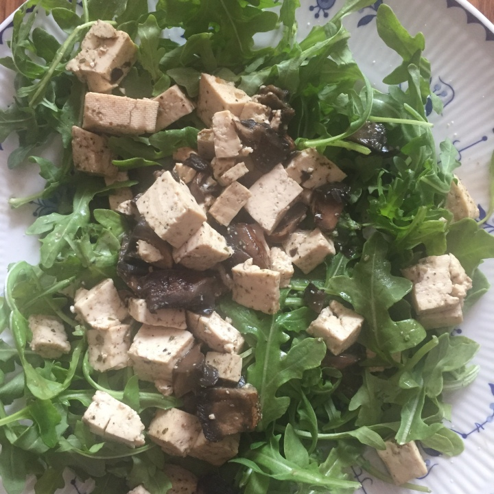 Tofu dish with mushrooms and broccoli on a bed of arugula