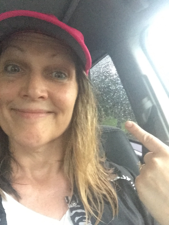 Female in car with baseball cap and wet hair